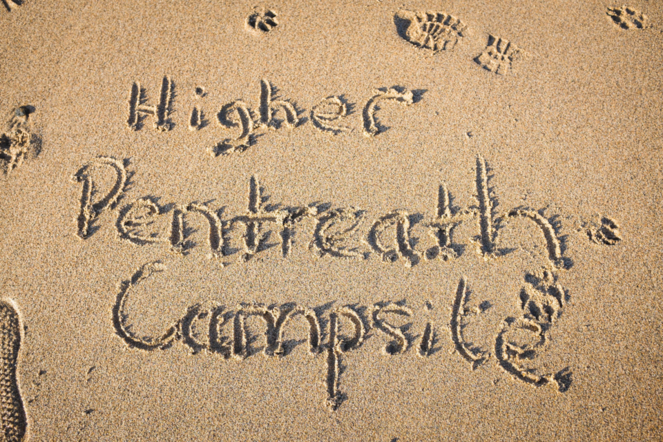 """Writing our name """"Higher Pentreath Campsite"""" in the golden sands of our nearest beach."""